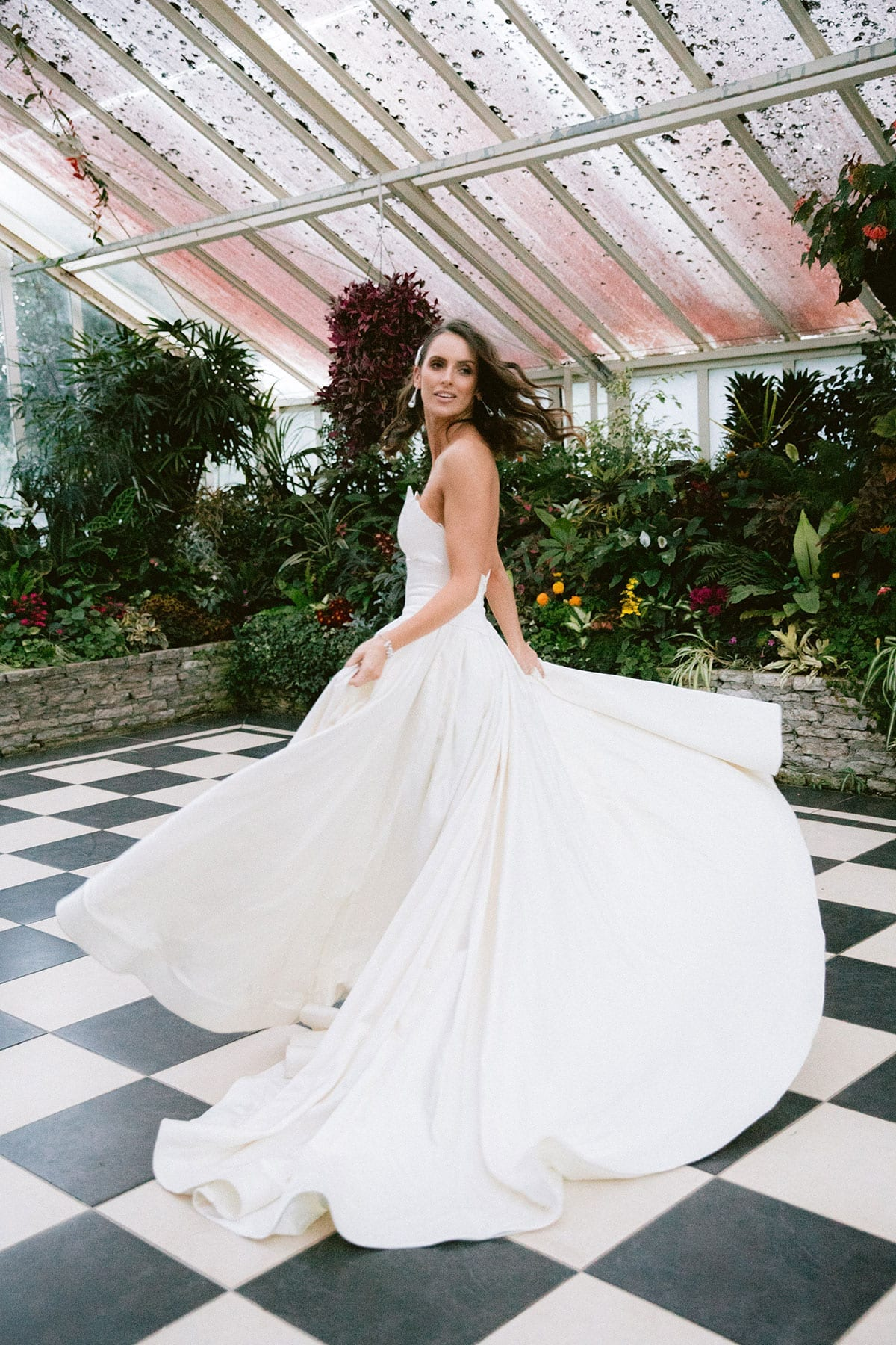 Model wearing Vinka Design Germaine Wedding Dress, a strapless dramatic wedding dress with split in a botanical garden greenhouse facing to the side dress flared