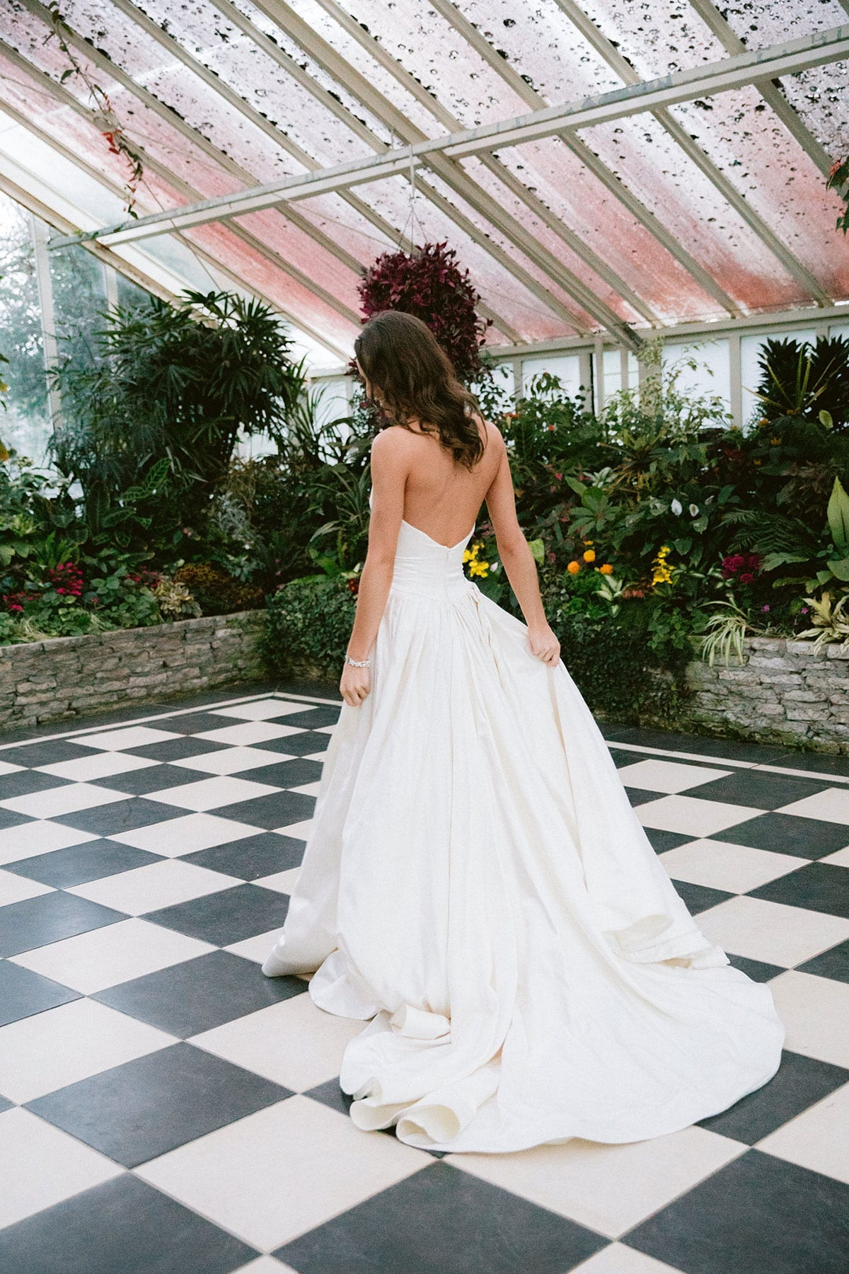 Model wearing Vinka Design Germaine Wedding Dress, a strapless dramatic wedding dress with split in a botanical garden greenhouse facing away with train along ground