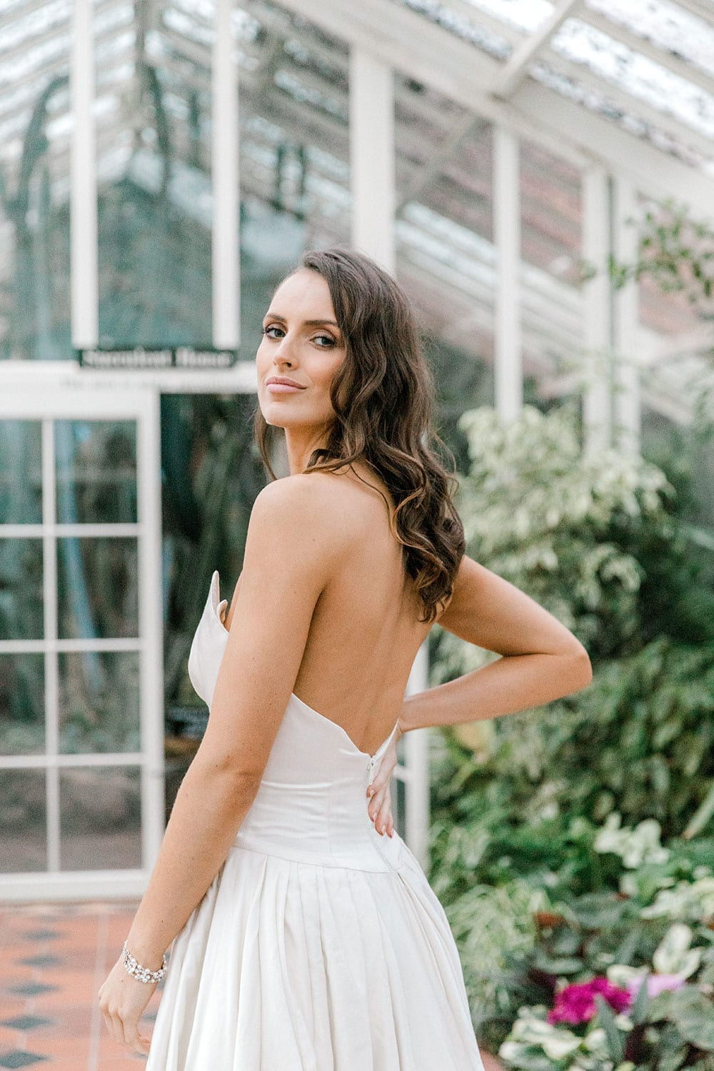 Model wearing Vinka Design Germaine Wedding Dress, a strapless dramatic wedding dress with split in a botanical garden greenhouse close up looking over shoulder