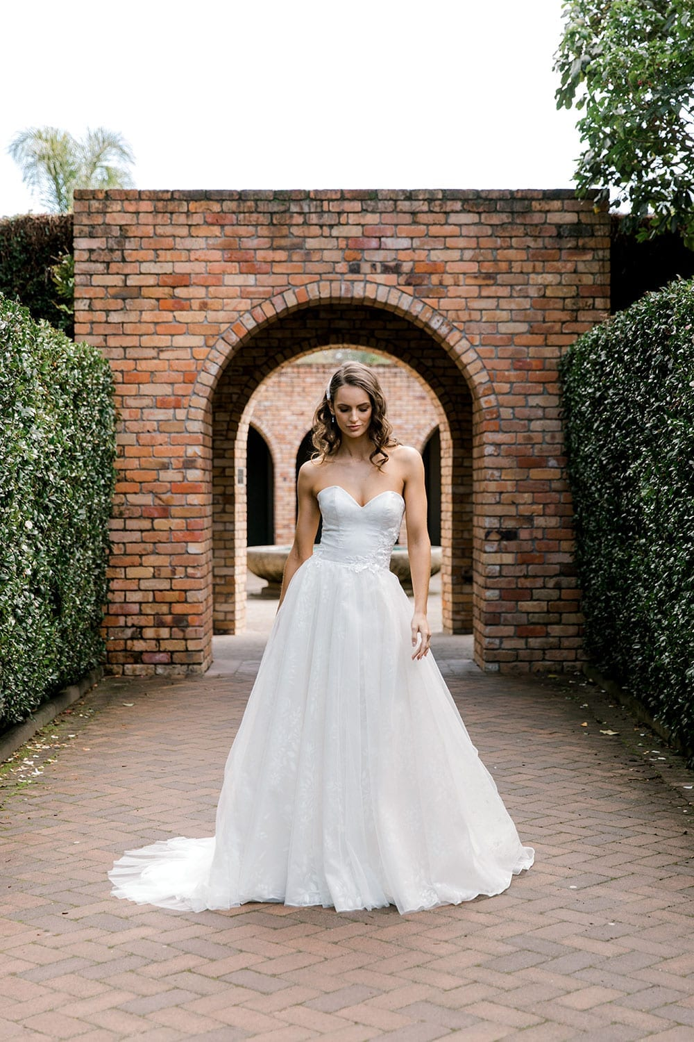 Model wearing Vinka Design Jasmine Wedding Dress, a Strapless Classic Wedding Gown in front of a garden brick arch