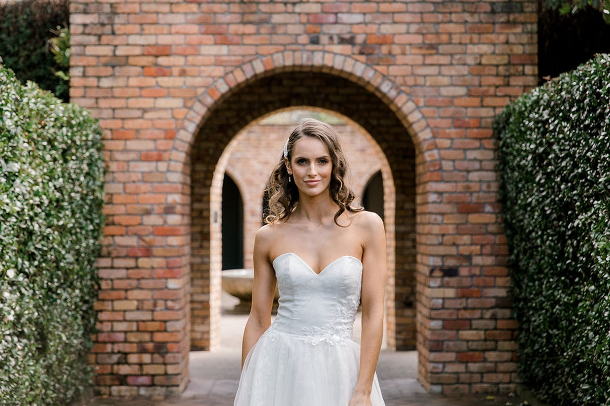 Model wearing Vinka Design Jasmine Wedding Dress, a Strapless Classic Wedding Gown close up in front of brick arches in a garden