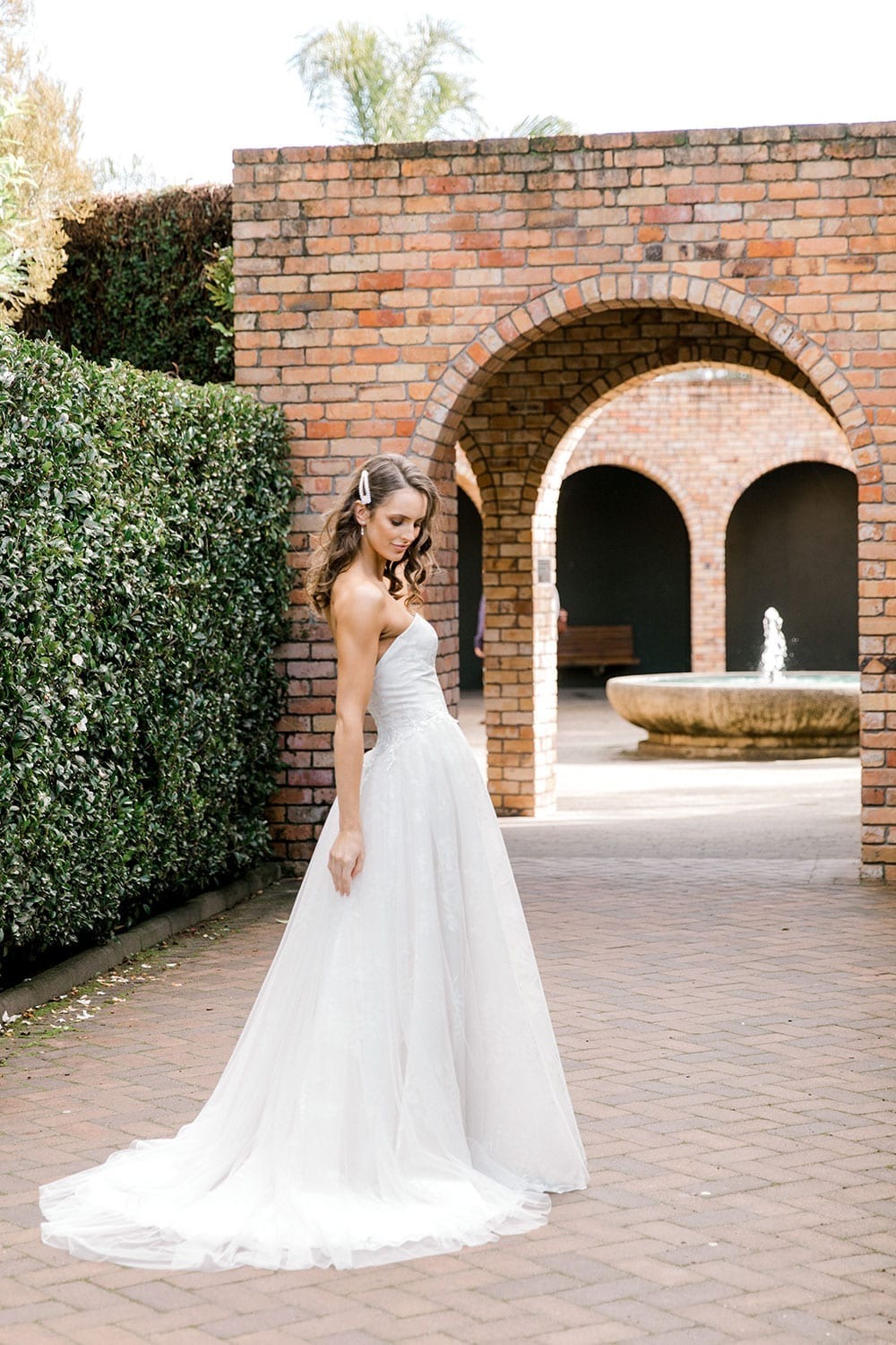 Model wearing Vinka Design Jasmine Wedding Dress, a Strapless Classic Wedding Gown at a side angle showing train in front of brick arches in a garden