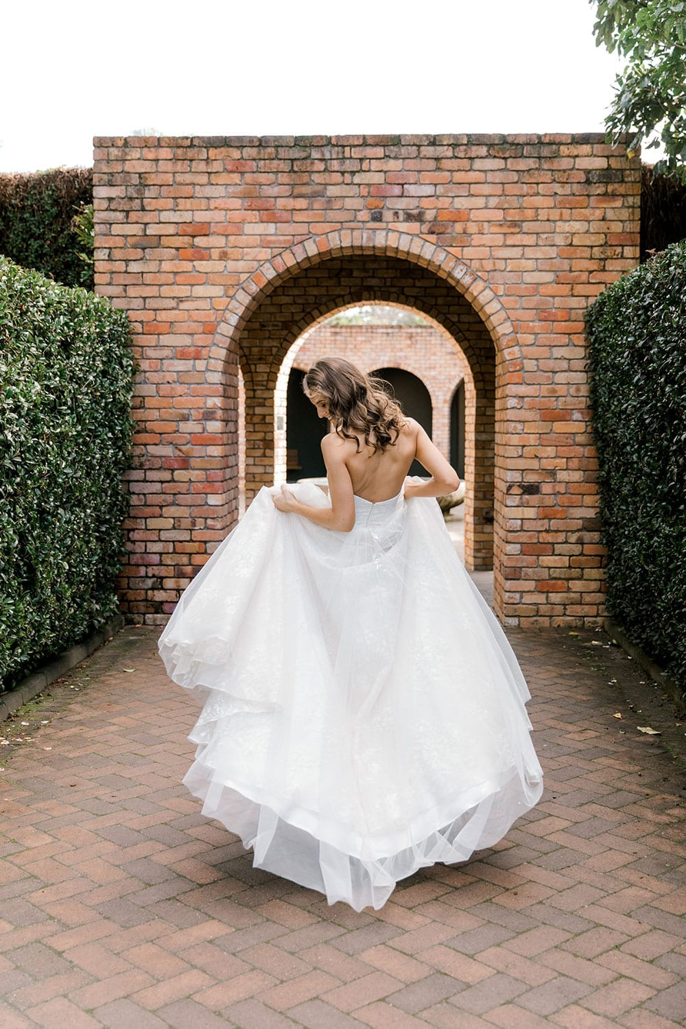 Model wearing Vinka Design Jasmine Wedding Dress, a Strapless Classic Wedding Gown facing away in front of brick arches in a garden
