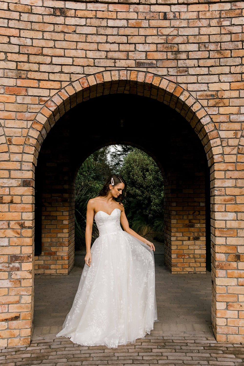 Model wearing Vinka Design Jasmine Wedding Dress, a Strapless Classic Wedding Gown facing down in front of a brick arch in a garden