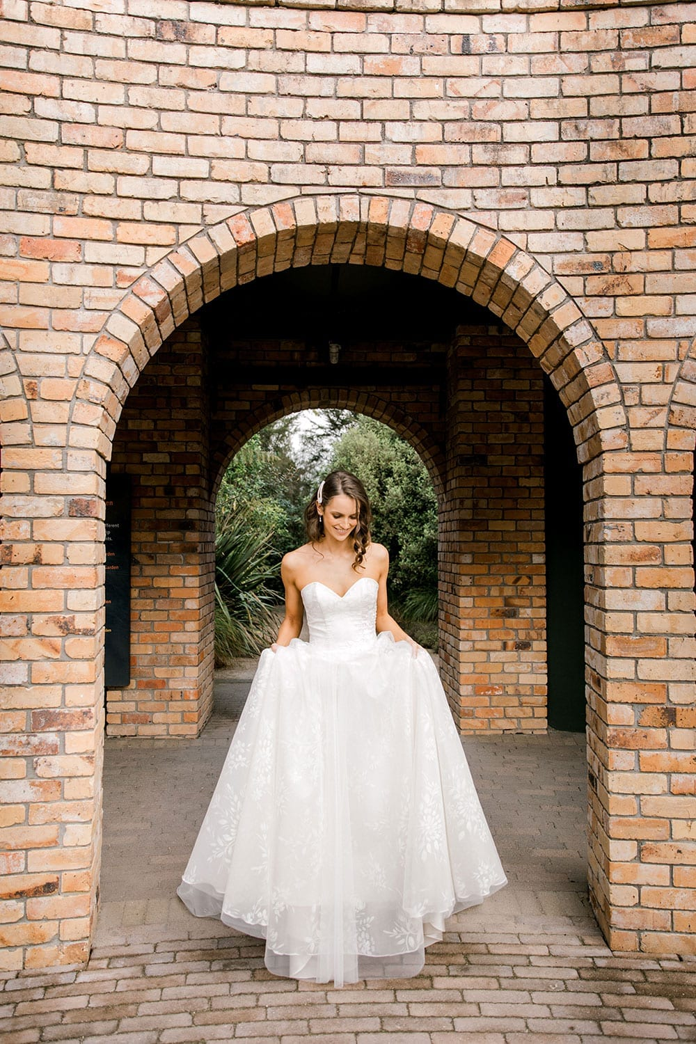 Model wearing Vinka Design Jasmine Wedding Dress, a Strapless Classic Wedding Gown holding out skirt in front of a brick arch in a garden