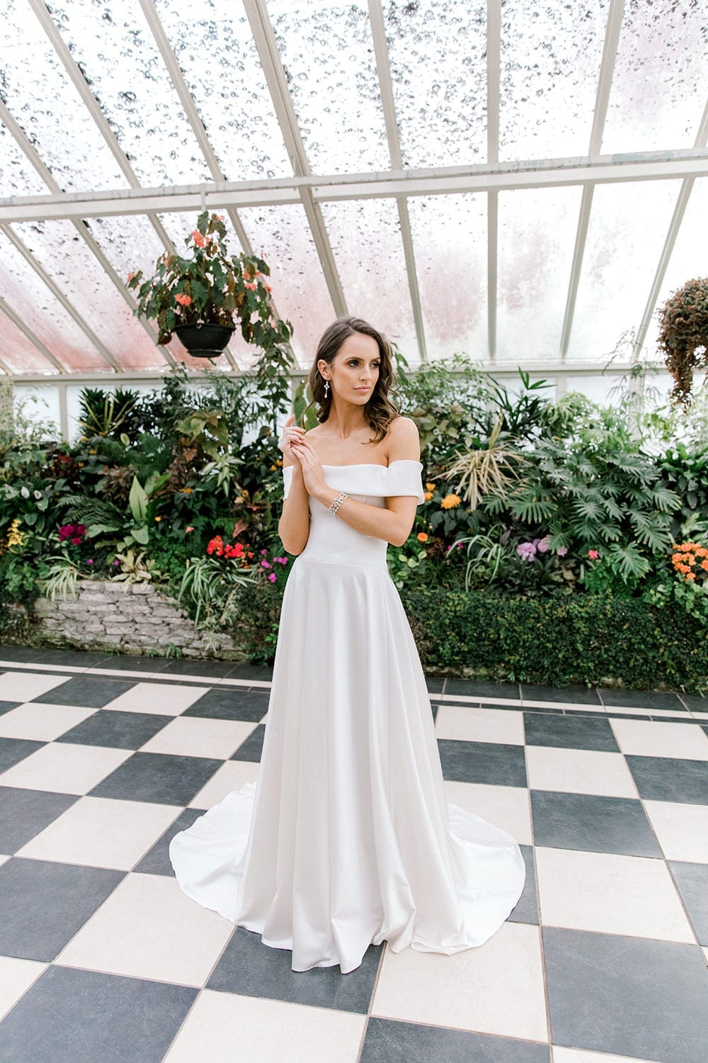 Model wearing Vinka Design Deor Wedding Dress, an Off-Shoulder Satin Wedding Gown inside botanical garden greenhouse
