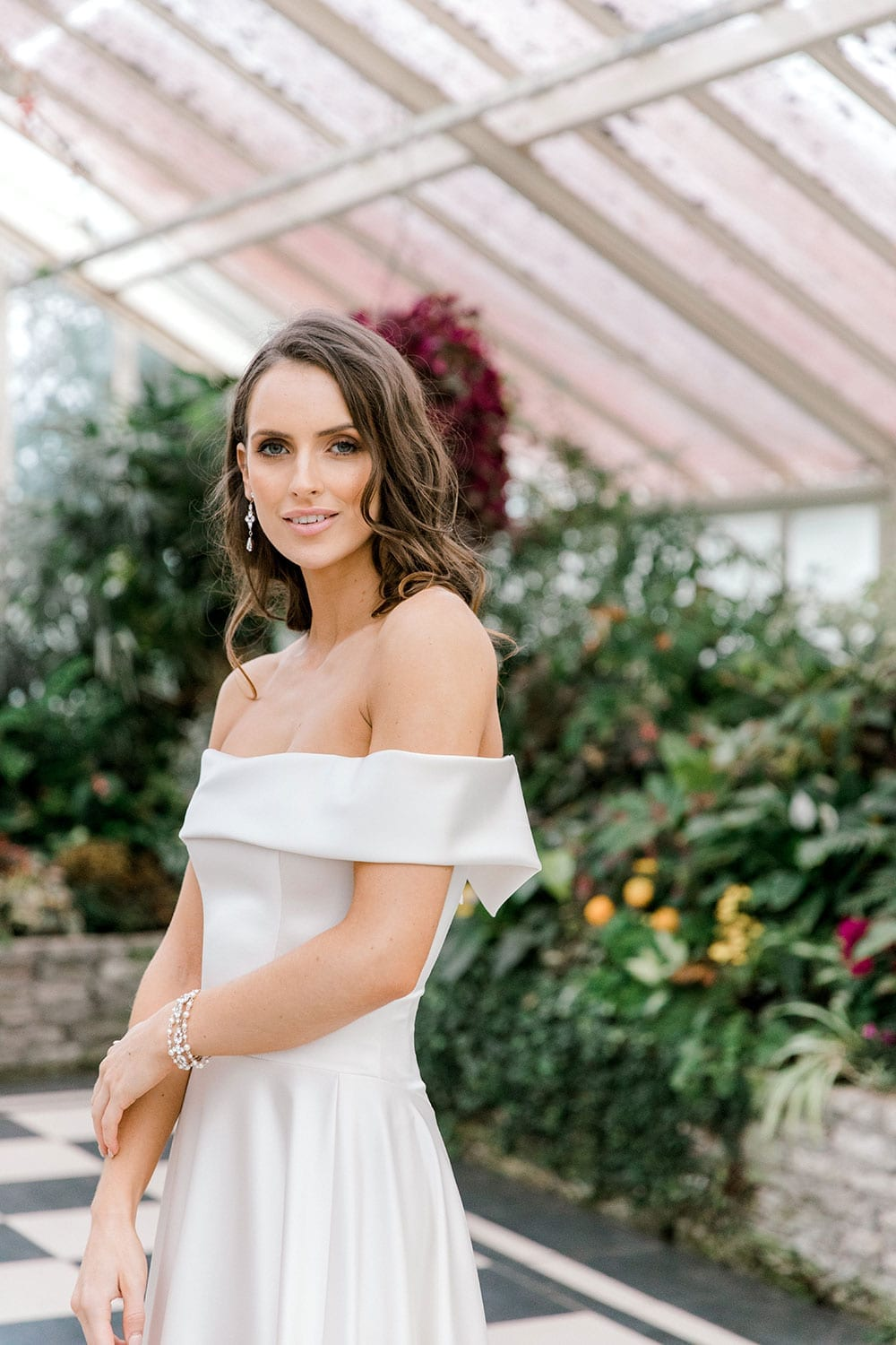 Model wearing Vinka Design Deor Wedding Dress, an Off-Shoulder Satin Wedding Gown side angled facing camera inside botanical garden greenhouse