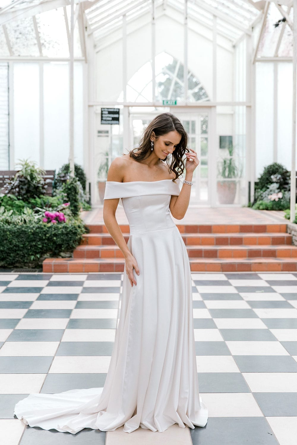 Model wearing Vinka Design Deor Wedding Dress, an Off-Shoulder Satin Wedding Gown portrait inside botanical garden greenhouse