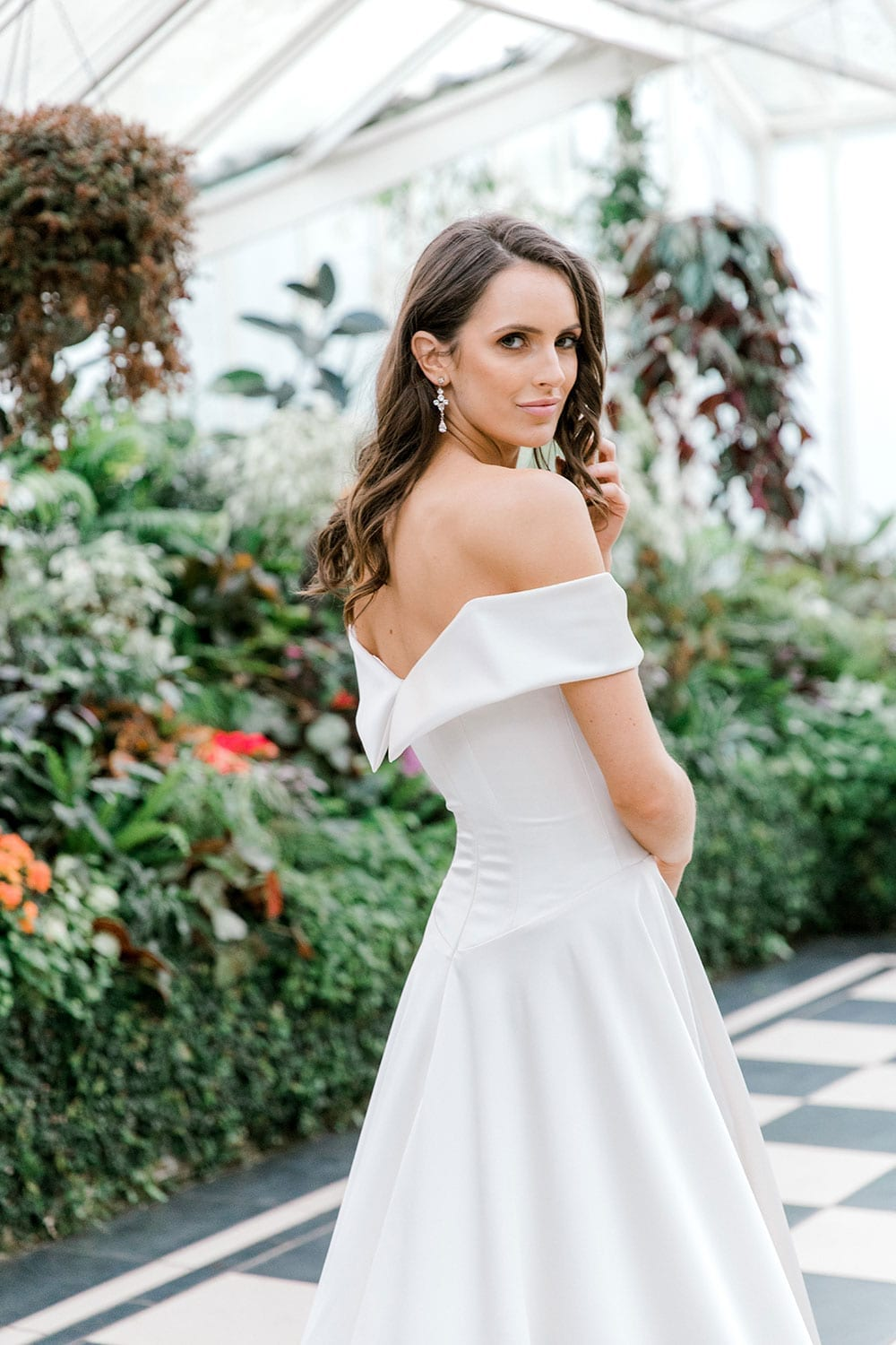 Model wearing Vinka Design Deor Wedding Dress, an Off-Shoulder Satin Wedding Gown facing away showing back of dress inside botanical garden greenhouse