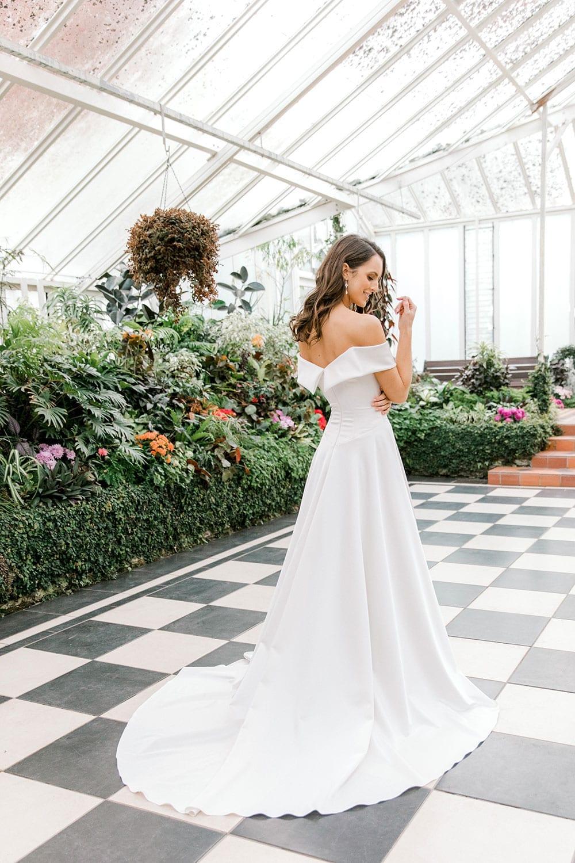 Model wearing Vinka Design Deor Wedding Dress, an Off-Shoulder Satin Wedding Gown facing away showing back of dress and train inside botanical garden greenhouse
