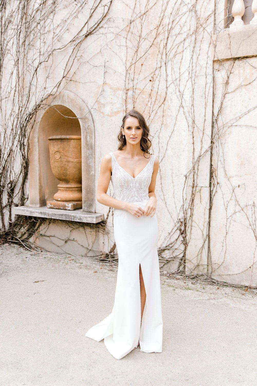 Model wearing Vinka Design Martina Wedding Dress, an Elegant Simple Wedding Gown in front of old building