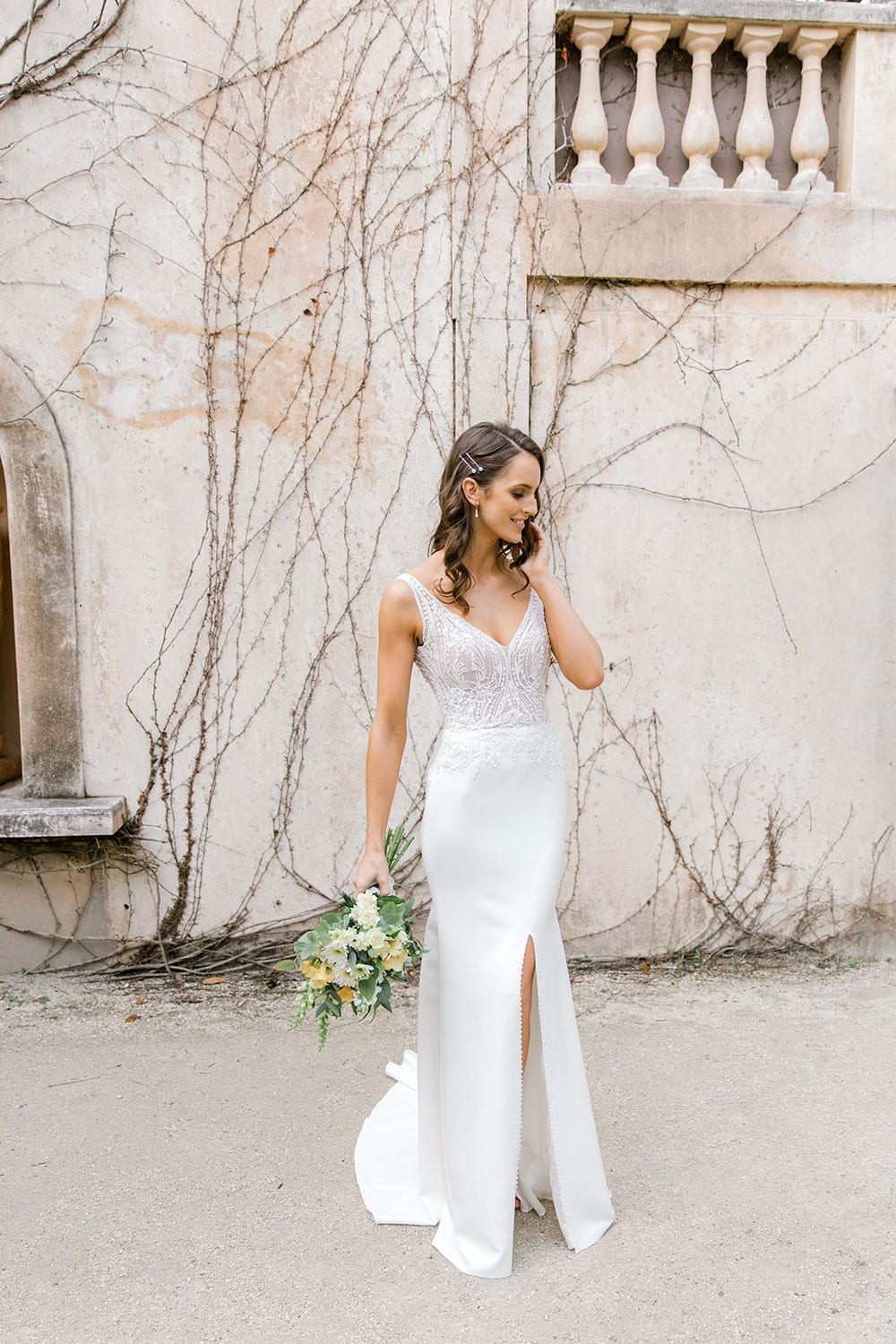 Model wearing Vinka Design Martina Wedding Dress, an Elegant Simple Wedding Gown in front of old building hand to head