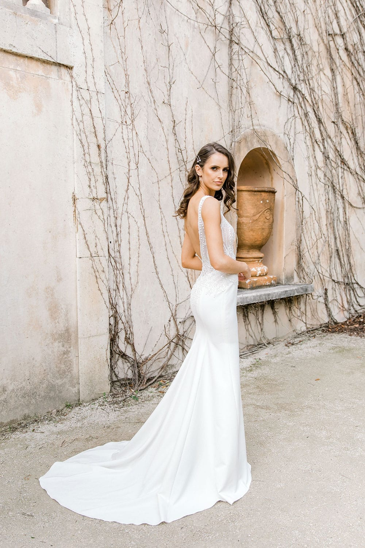 Model wearing Vinka Design Martina Wedding Dress, an Elegant Simple Wedding Gown in front of old building facing away showing dress train