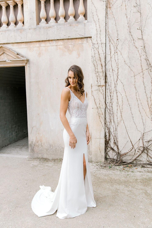 Model wearing Vinka Design Martina Wedding Dress, an Elegant Simple Wedding Gown in front of old building side angle
