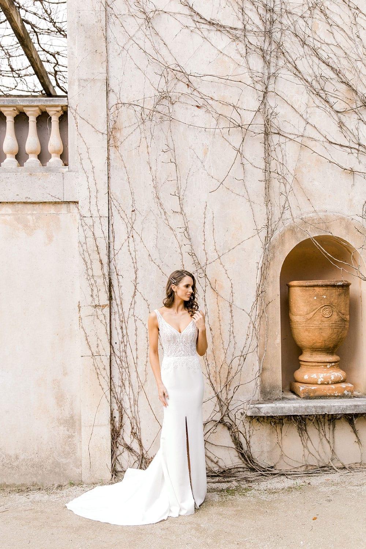Model wearing Vinka Design Martina Wedding Dress, an Elegant Simple Wedding Gown in front of old building foot on step