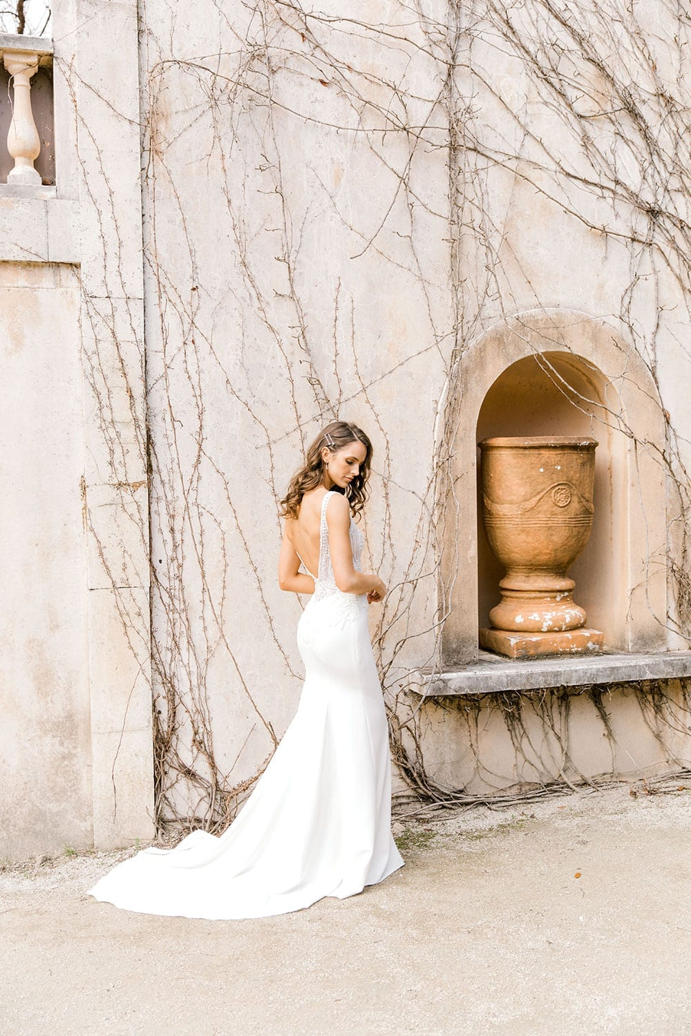 Model wearing Vinka Design Martina Wedding Dress, an Elegant Simple Wedding Gown in front of old building facing away with dress train displayed