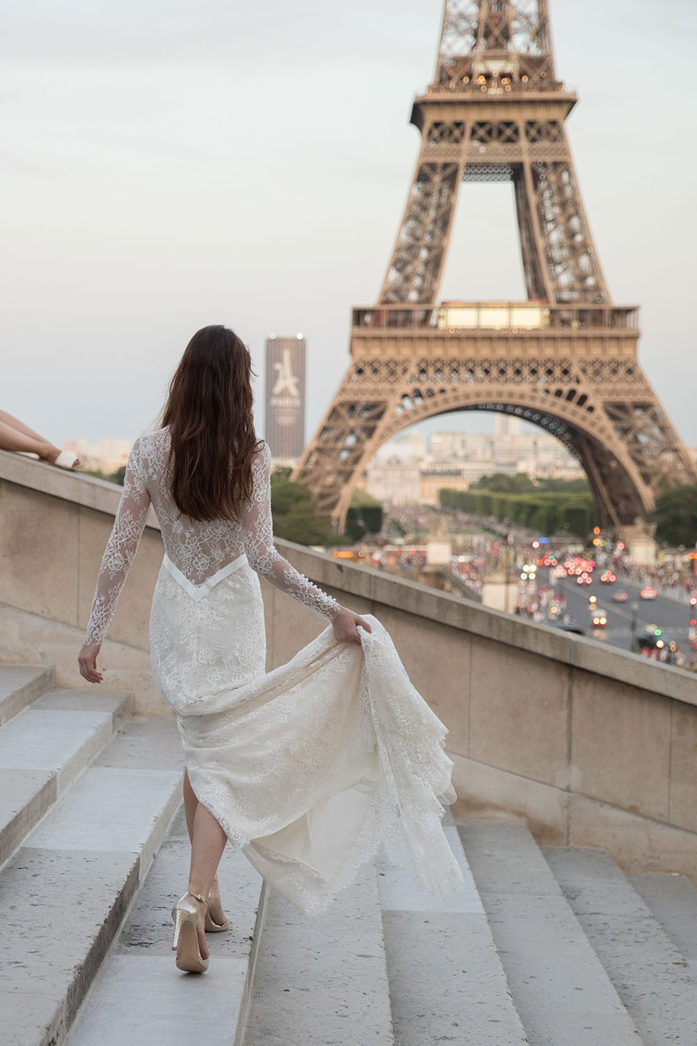 Model wearing Vinka Design Deanna Wedding Dress, a Lace Wedding Gown with Sleeves on steps looking towards the Eiffel Tower in Paris