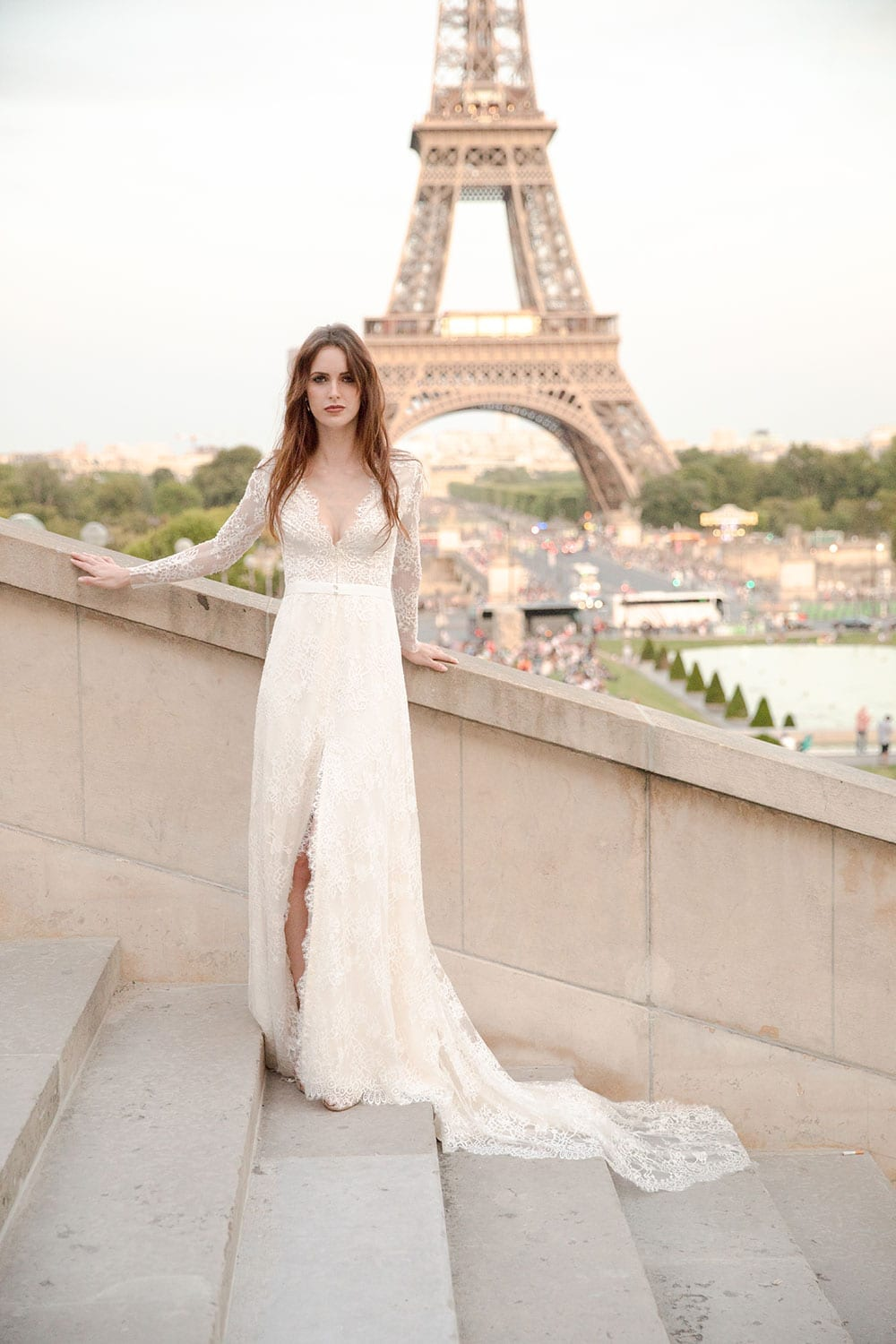 Model wearing Vinka Design Deanna Wedding Dress, a Lace Wedding Gown with Sleeves dress flowing down steps in front of the Eiffel Tower in Paris