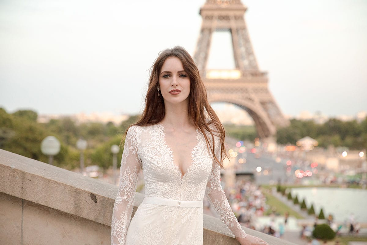 Model wearing Vinka Design Deanna Wedding Dress, a Lace Wedding Gown with Sleeves close up of front with lace scalloped edges in front of the Eiffel Tower in Paris