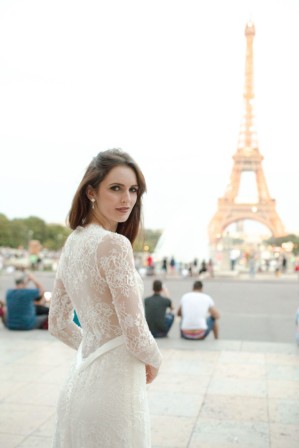 Model wearing Vinka Design Deanna Wedding Dress, a Lace Wedding Gown with Sleeves facing towards the Eiffel Tower in Paris
