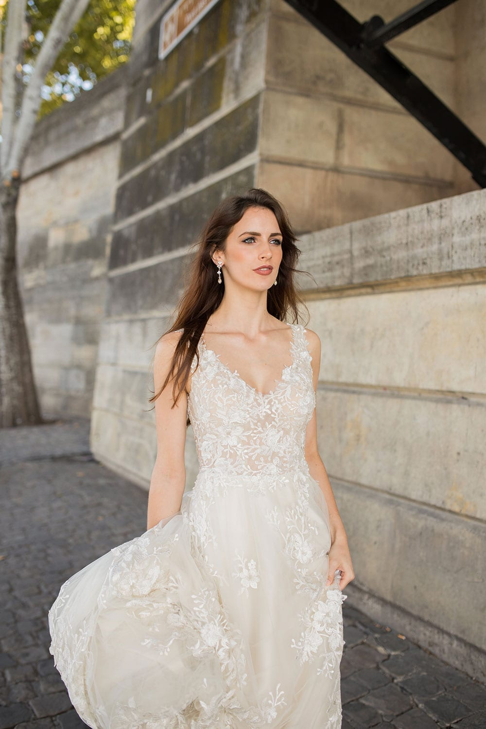 Model wearing Vinka Design Delta Wedding Dress, a Sheer Embroidered Lace Wedding Gown next to the Seine in Paris