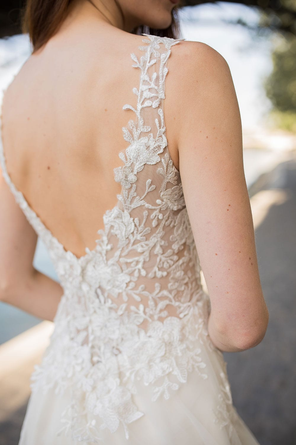 Model wearing Vinka Design Delta Wedding Dress, a Sheer Embroidered Lace Wedding Gown close up showing low back next to the Seine in Paris