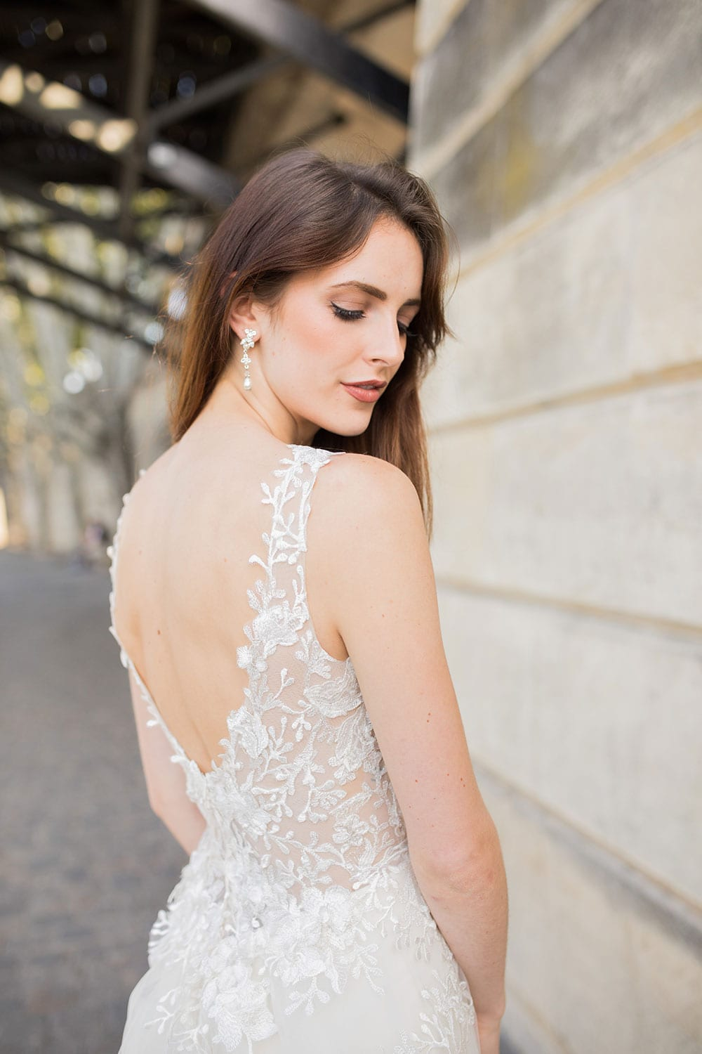 Model wearing Vinka Design Delta Wedding Dress, a Sheer Embroidered Lace Wedding Gown showing low back detail next to the Seine in Paris