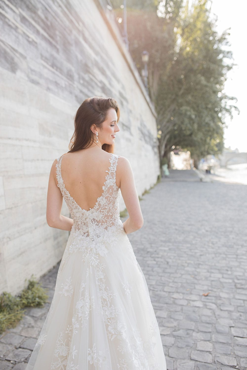 Model wearing Vinka Design Delta Wedding Dress, a Sheer Embroidered Lace Wedding Gown facing away showing back on path next to the Seine in Paris