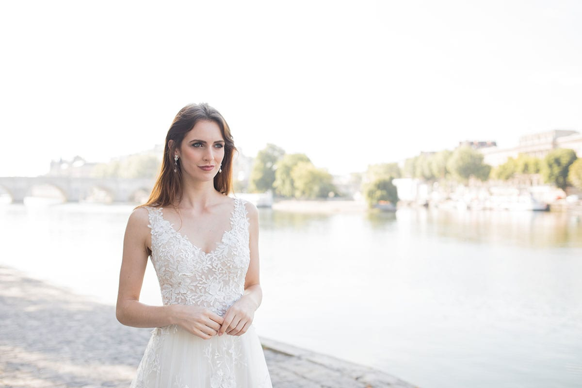 Model wearing Vinka Design Delta Wedding Dress, a Sheer Embroidered Lace Wedding Gown close up showing lace front detail next to the Seine in Paris