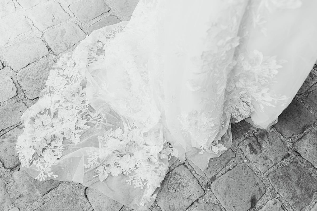 Close up of dress lace detail of Vinka Design Delta Wedding Dress, a Sheer Embroidered Lace Wedding Gown on path
