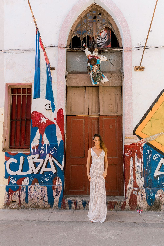 Model wearing Vinka Design Alexia Wedding Dress, a Semi Sheer Beaded Lace Wedding Gown on Street in Havana with Cuba flag