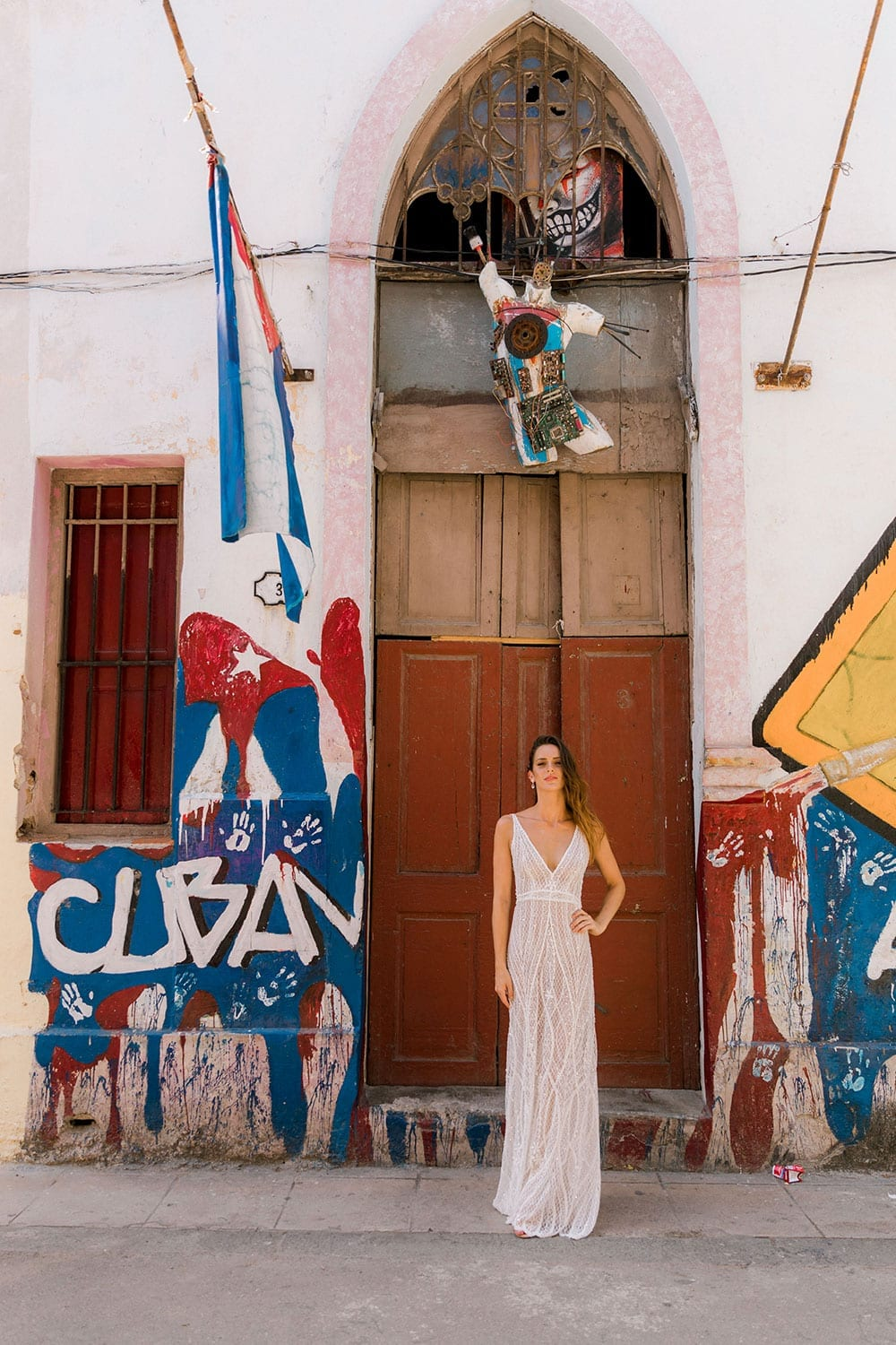Model wearing Vinka Design Alexia Wedding Dress, a Semi Sheer Beaded Lace Wedding Gown in front of arch on Street in Havana with Cuba flag