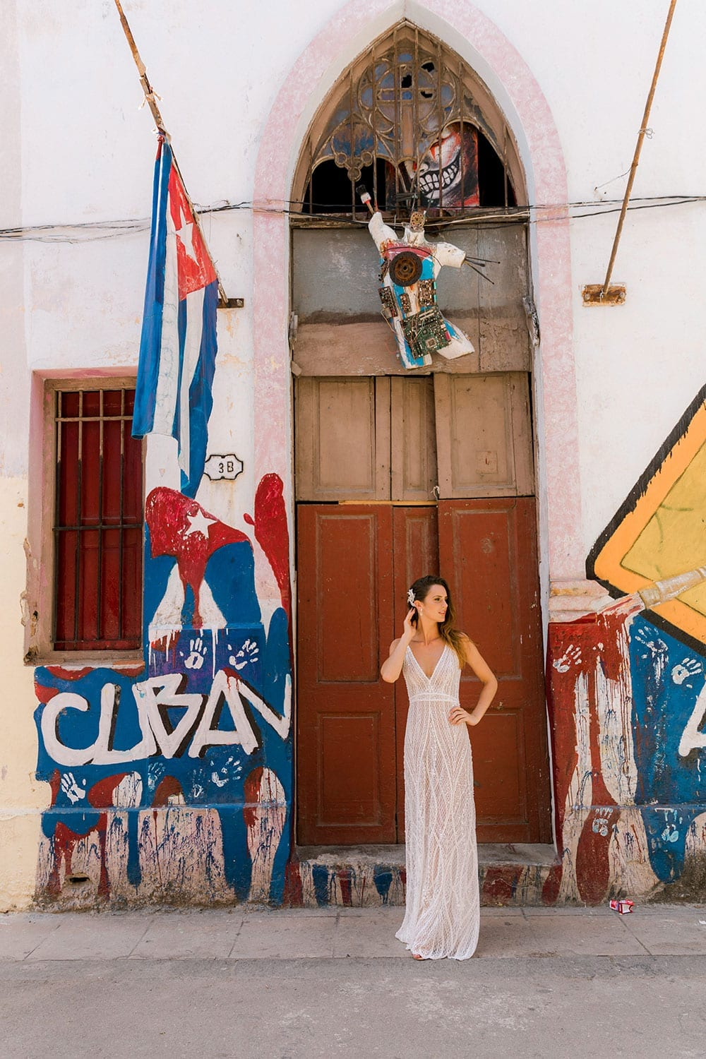 Model wearing Vinka Design Alexia Wedding Dress, a Semi Sheer Beaded Lace Wedding Gown hand raised to head in front of arch on Street in Havana with Cuba flag