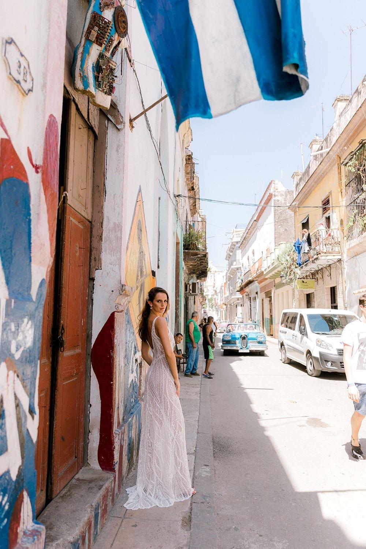 Model wearing Vinka Design Alexia Wedding Dress, a Semi Sheer Beaded Lace Wedding Gown looking down street in Havana with Cuba flag overhead