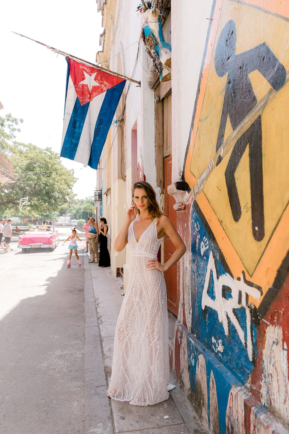 Model wearing Vinka Design Alexia Wedding Dress, a Semi Sheer Beaded Lace Wedding Gown on Havan street with flag and roadsign