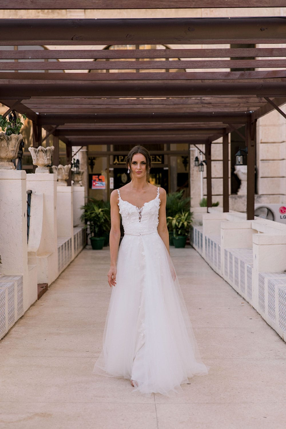 Model wearing Vinka Design Alicia Wedding Dress, a Embroidered Wedding Gown & Skirt in the entrance to the Hotel Nacional in Havana Cuba