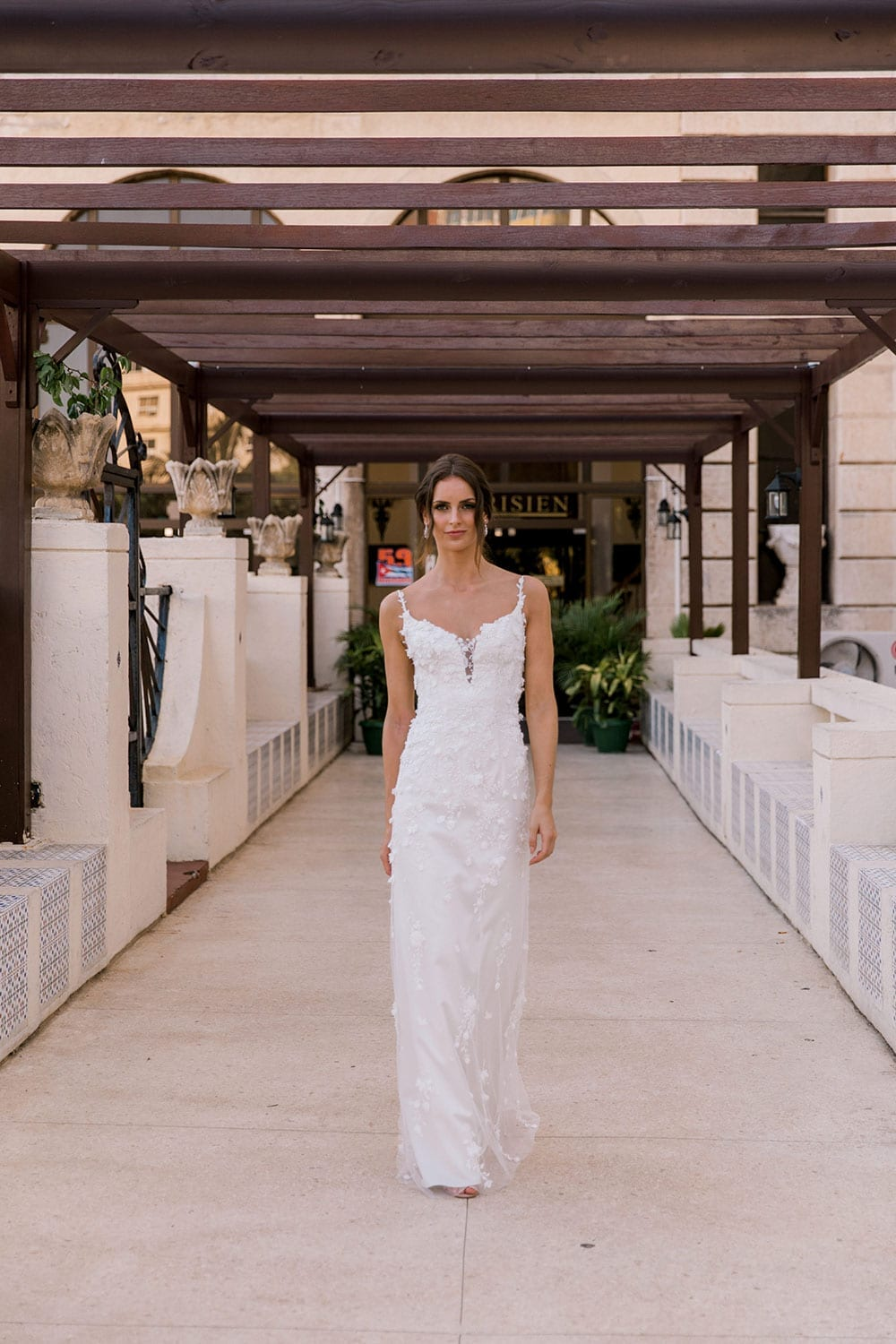 Model wearing Vinka Design Alicia Wedding Dress, a Embroidered Wedding Gown with skirt removed in the entrance to the Hotel Nacional in Havana Cuba