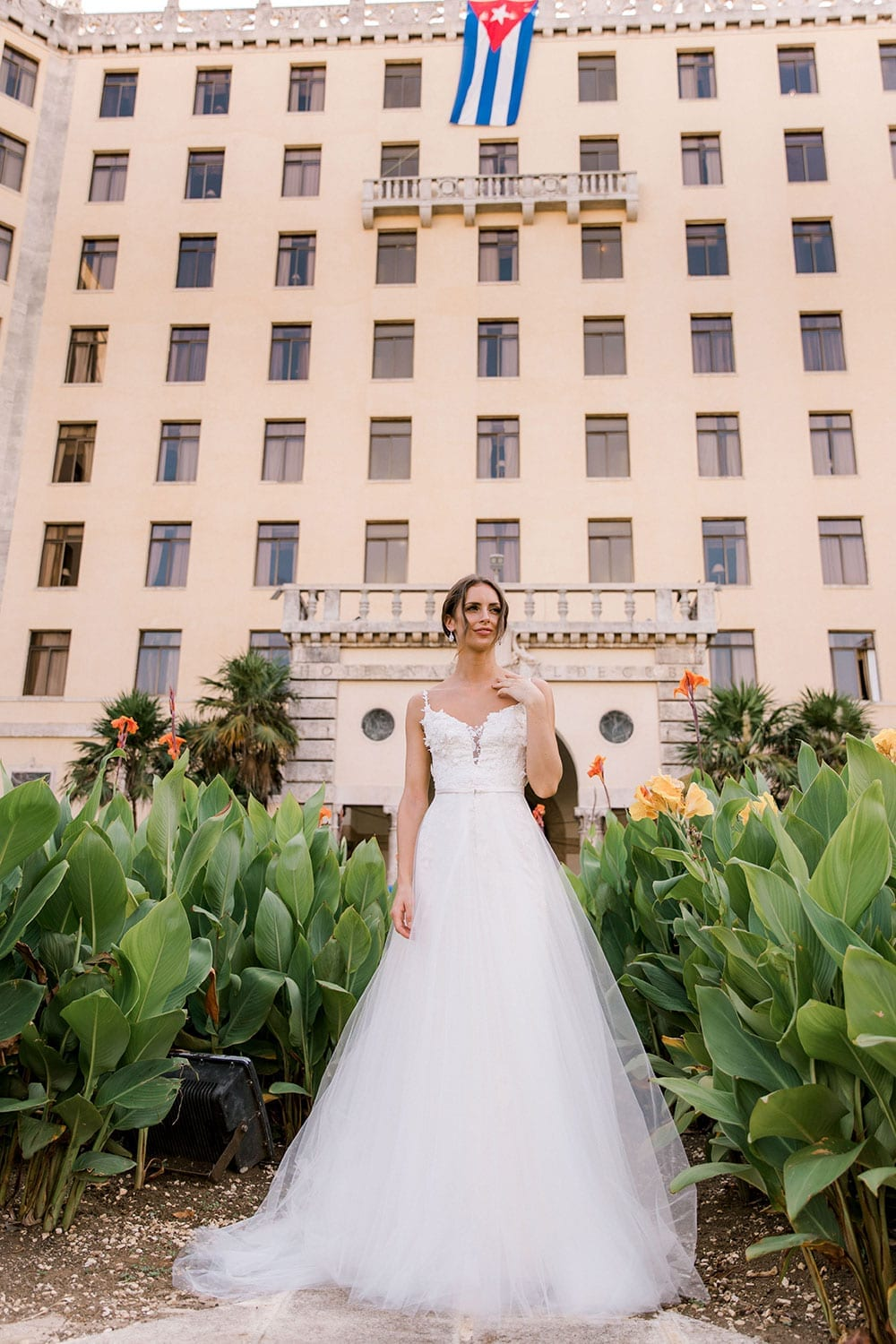 Model wearing Vinka Design Alicia Wedding Dress, a Embroidered Wedding Gown & skirt portrait in front the Hotel Nacional in Havana Cuba