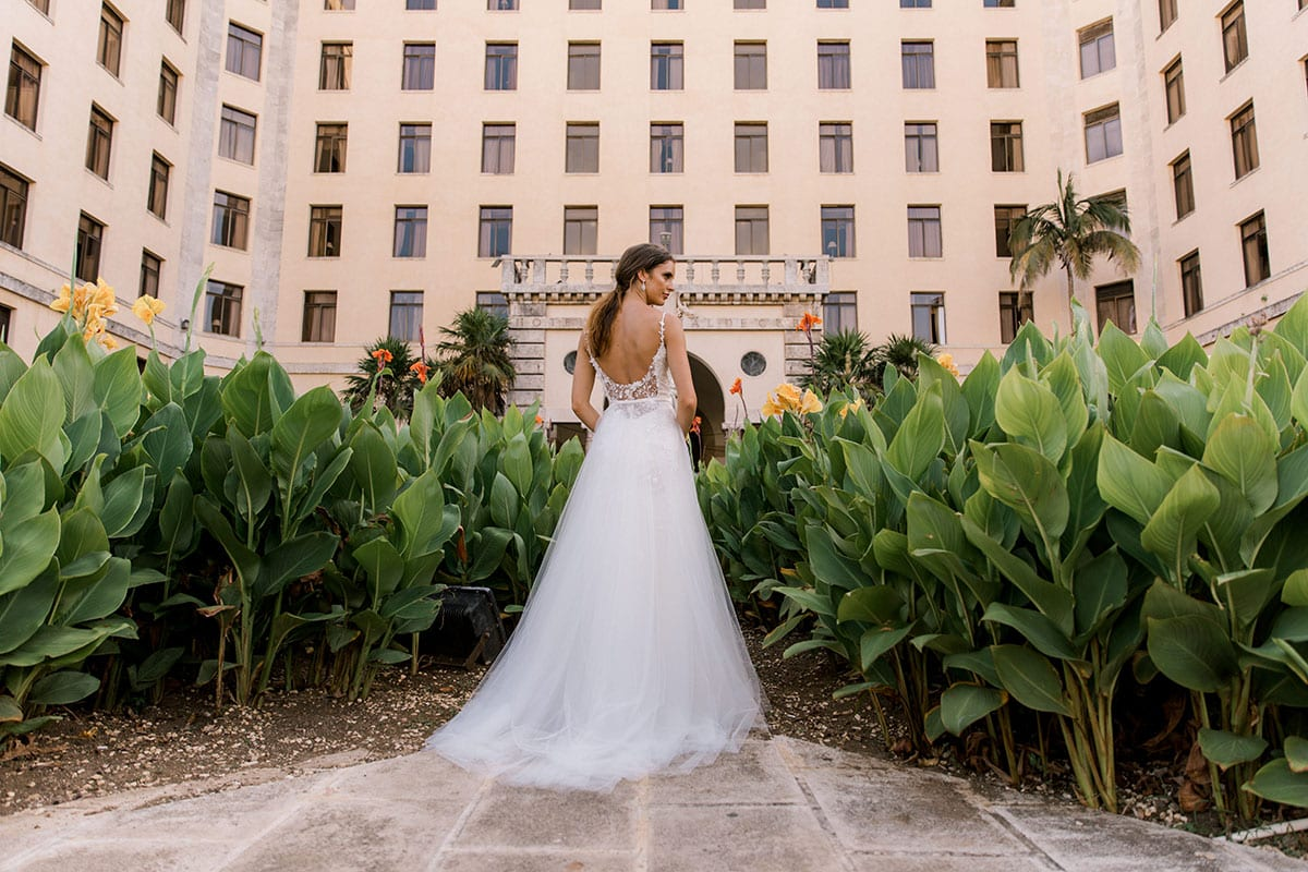 Model wearing Vinka Design Alicia Wedding Dress, a Embroidered Wedding Gown & skirt landscape in front the Hotel Nacional in Havana Cuba