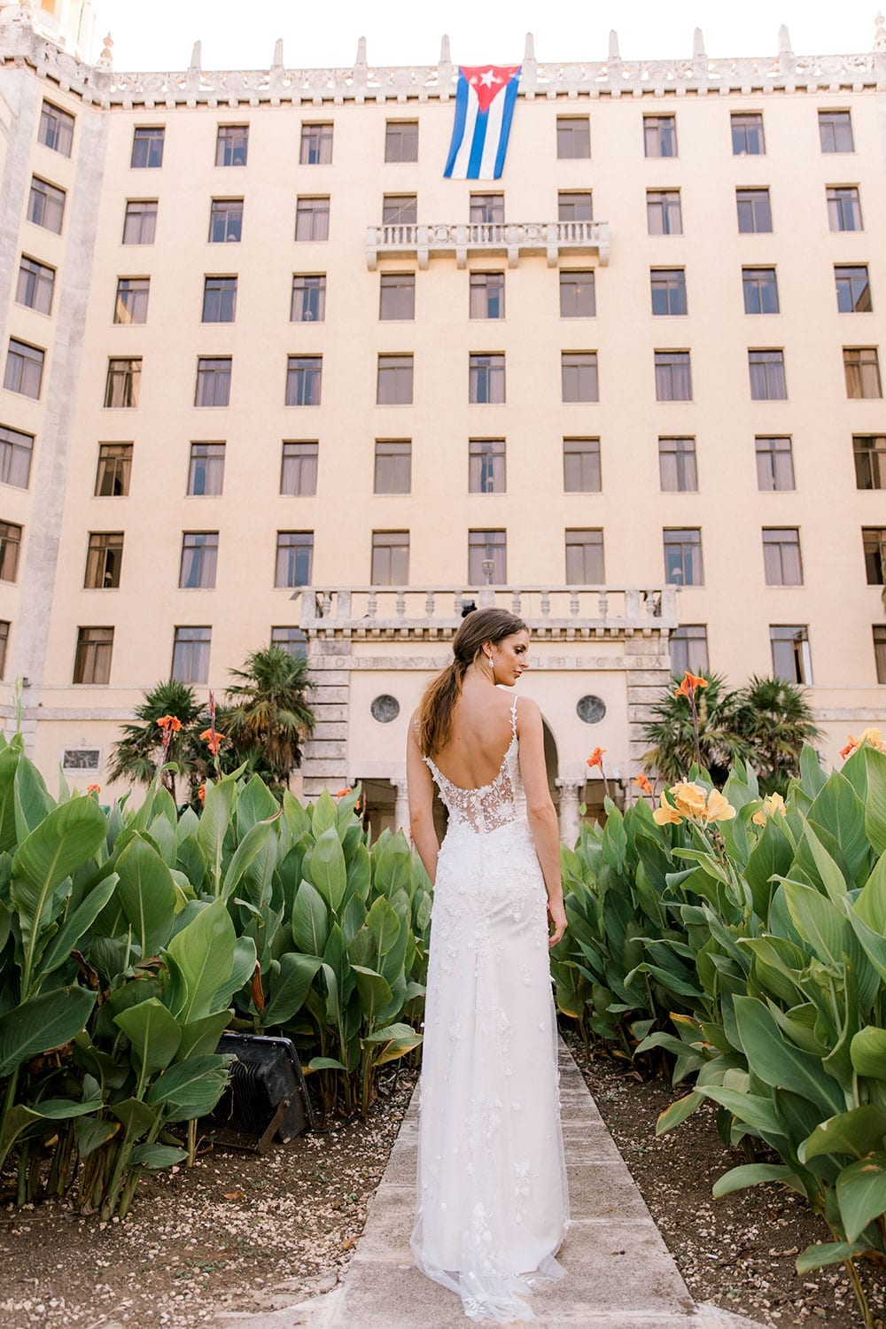 Model wearing Vinka Design Alicia Wedding Dress, a Embroidered Wedding Gown with the skirt removed landscape in front the Hotel Nacional in Havana Cuba