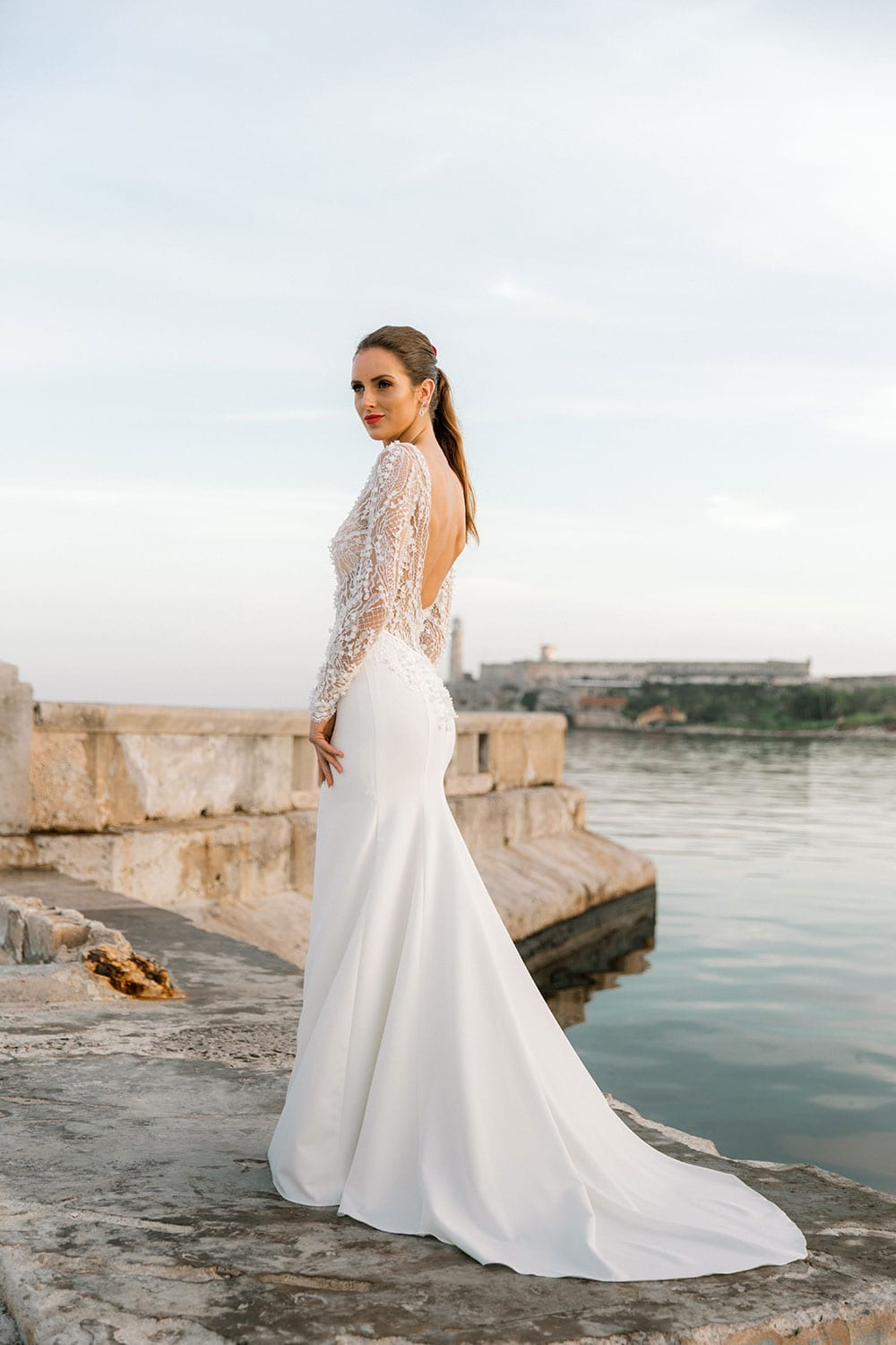 Model wearing Vinka Design Angela Wedding Dress, Fitted Wedding Gown with Lace Bodice posed next to the water with dress showing train, in Havana