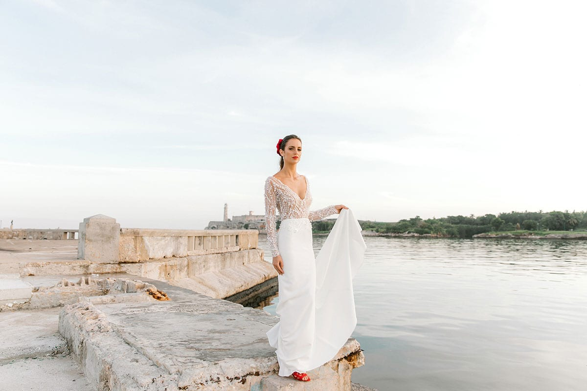 Model wearing Vinka Design Angela Wedding Dress, Fitted Wedding Gown with Lace Bodice posed next to the water with train in hand, in Havana