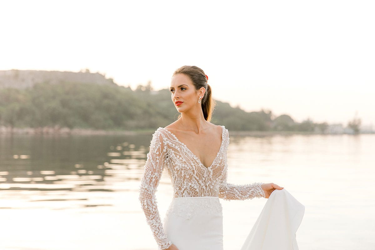 Model wearing Vinka Design Angela Wedding Dress, Fitted Wedding Gown with Lace Bodice next to the water in Havana close up of bodice with low v neck