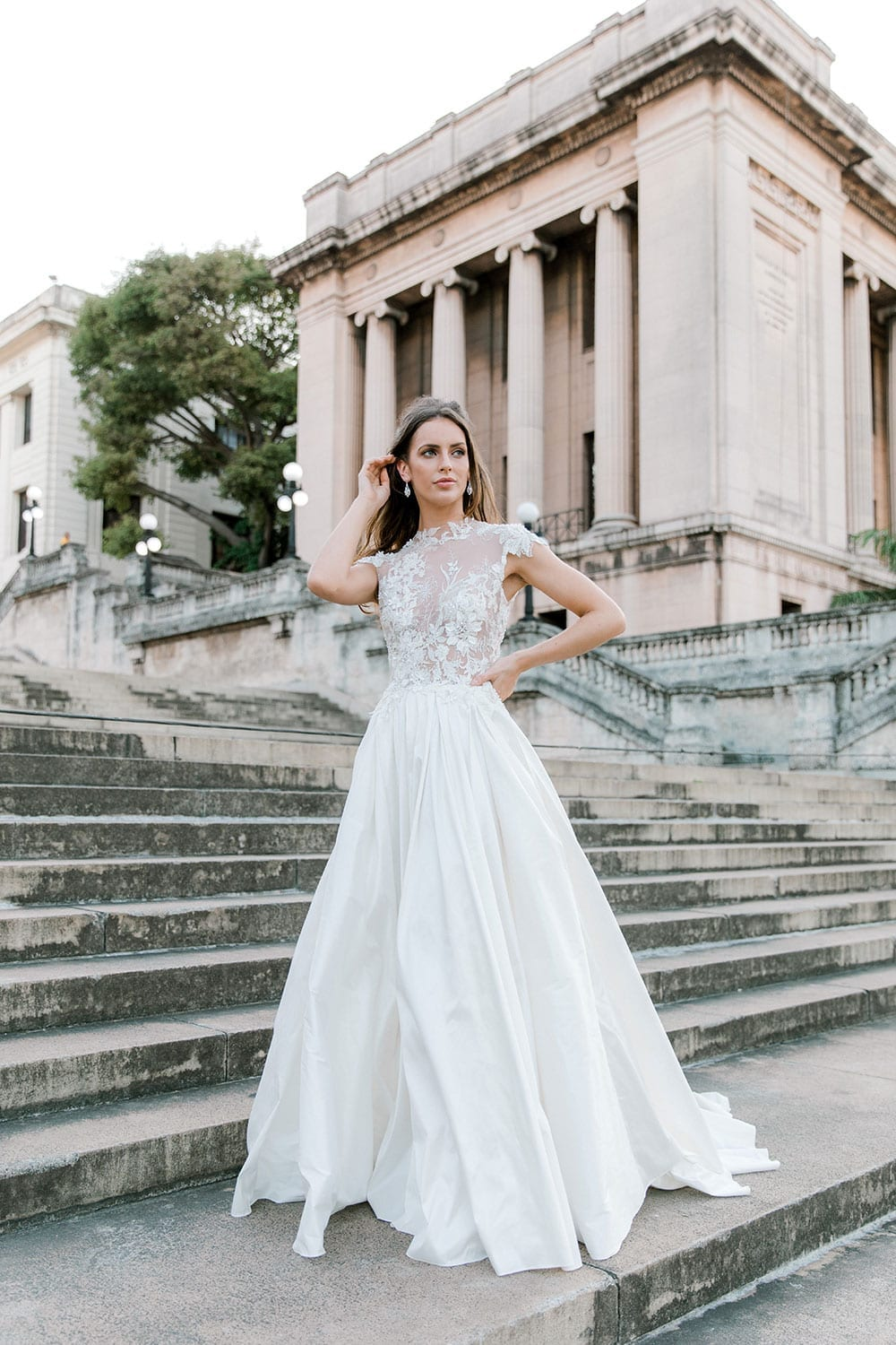 Model wearing Vinka Design Annalie Wedding Dress, a Beaded Lace High Neck Silk Wedding Gown in front of steps in Havana