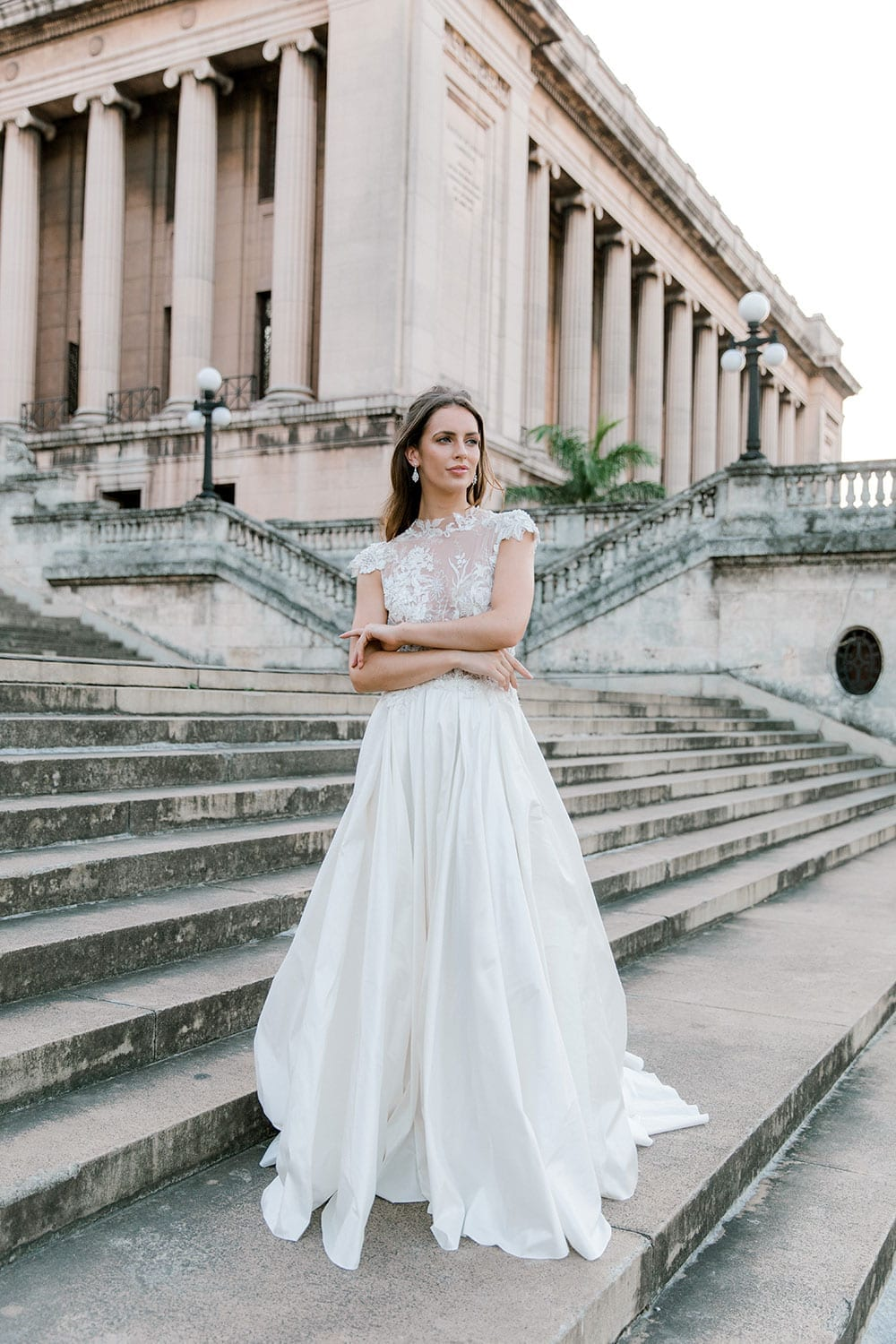 Model wearing Vinka Design Annalie Wedding Dress, a Beaded Lace High Neck Silk Wedding Gown on steps in Havana with old building in background