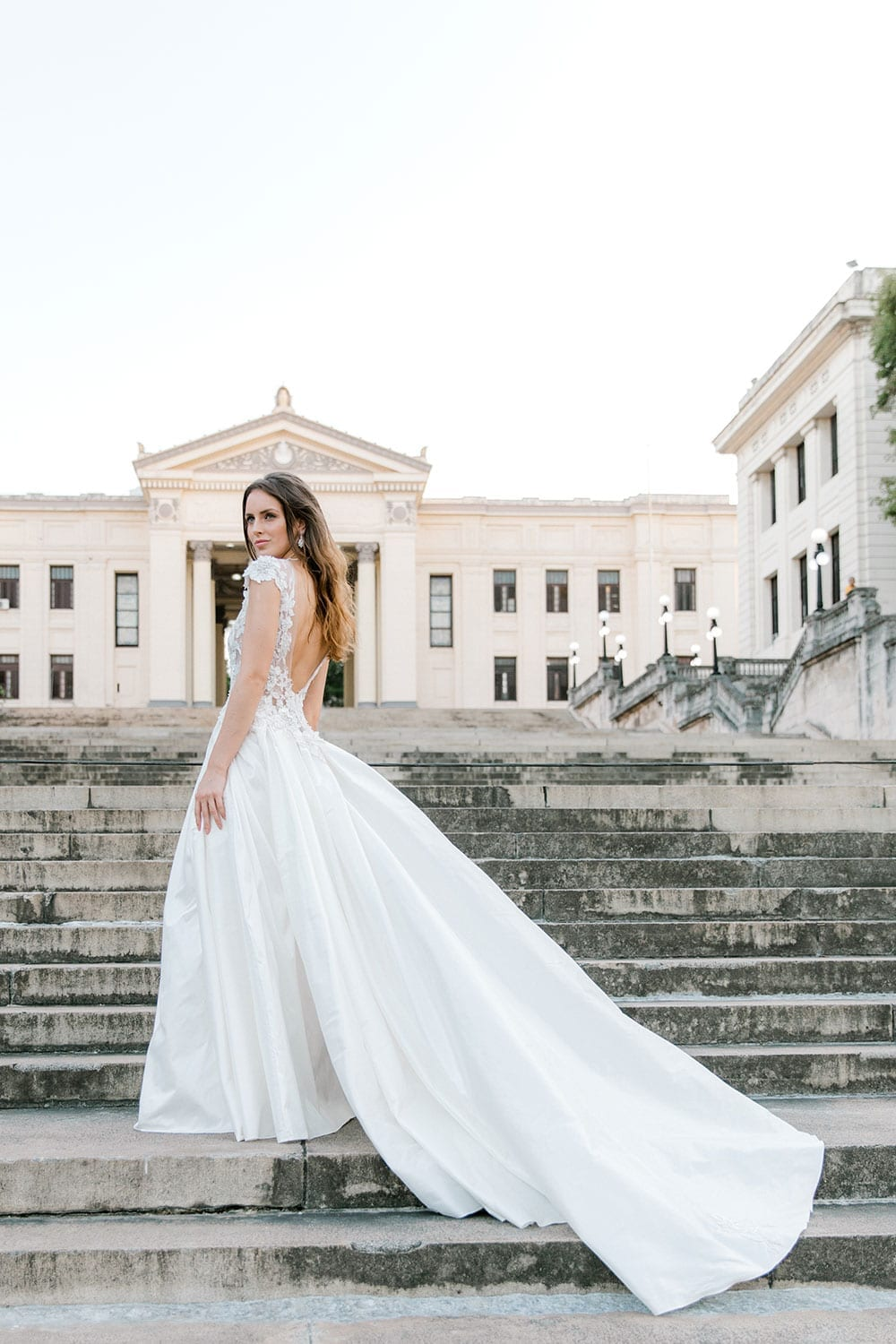 Model wearing Vinka Design Annalie Wedding Dress, a Beaded Lace High Neck Silk Wedding Gown on steps in Havana with dress flowing