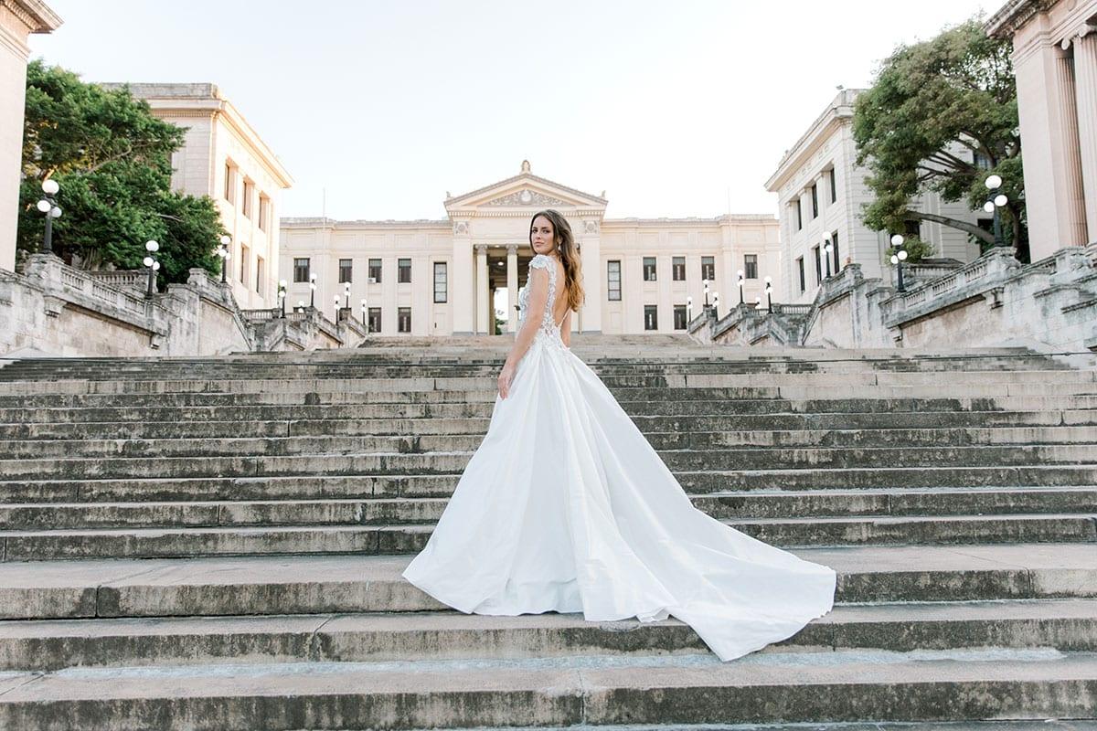 Model wearing Vinka Design Annalie Wedding Dress, a Beaded Lace High Neck Silk Wedding Gown on steps in Havana