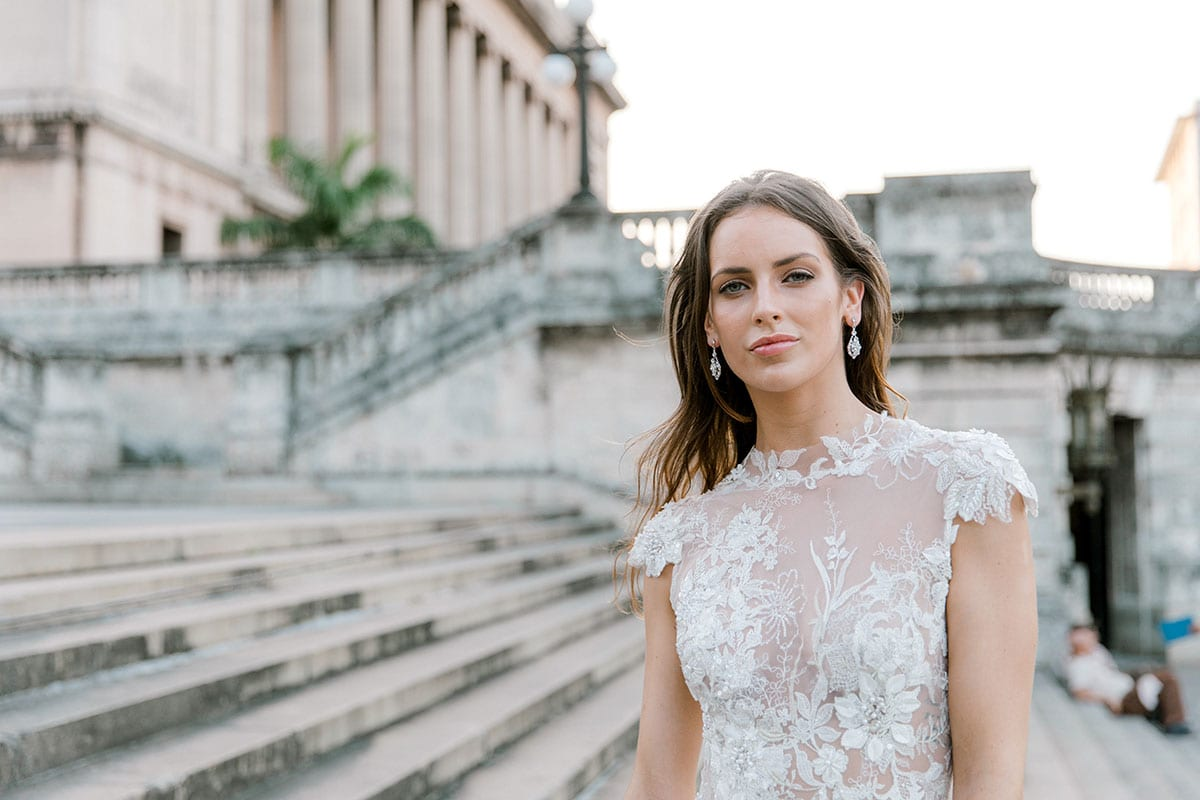 Model wearing Vinka Design Annalie Wedding Dress, a Beaded Lace High Neck Silk Wedding Gown on steps in Havana close up of front detail