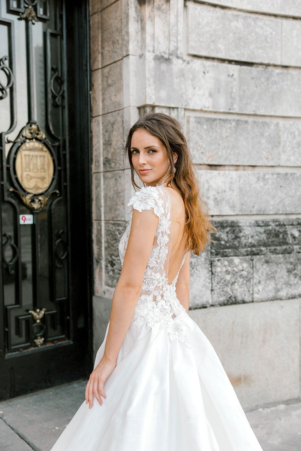 Model wearing Vinka Design Annalie Wedding Dress, a Beaded Lace High Neck Silk Wedding Gown on steps in Havana close up of back detail