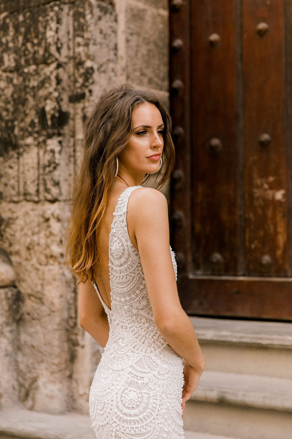 Model wearing Vinka Design Carlotta Wedding Dress, a V-Neck Beaded Mermaid Dress on the streets of Havana in front of an old wooden door